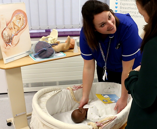 Midwife demonstrating safer sleeping